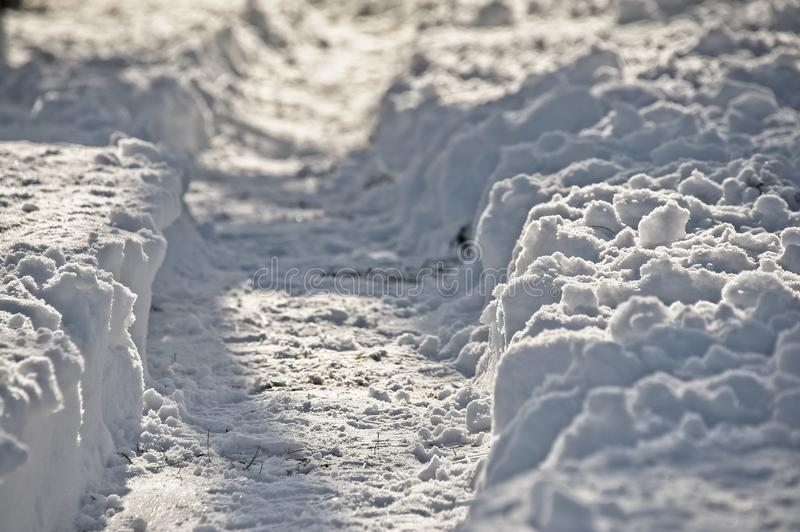 Cleared path in snow. Narrow path cleared in fresh snow on sunny day stock photography