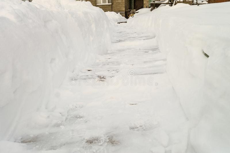 Cleared snowy footpath after heavy snowstorm. Winter passage to a suburban house royalty free stock photography