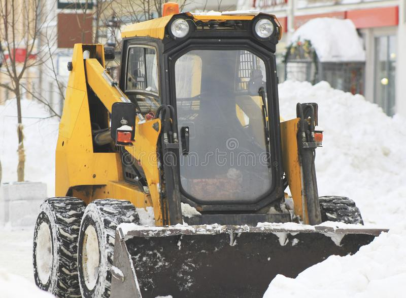 Clearing snow from the road with bulldozer in the city stock photography