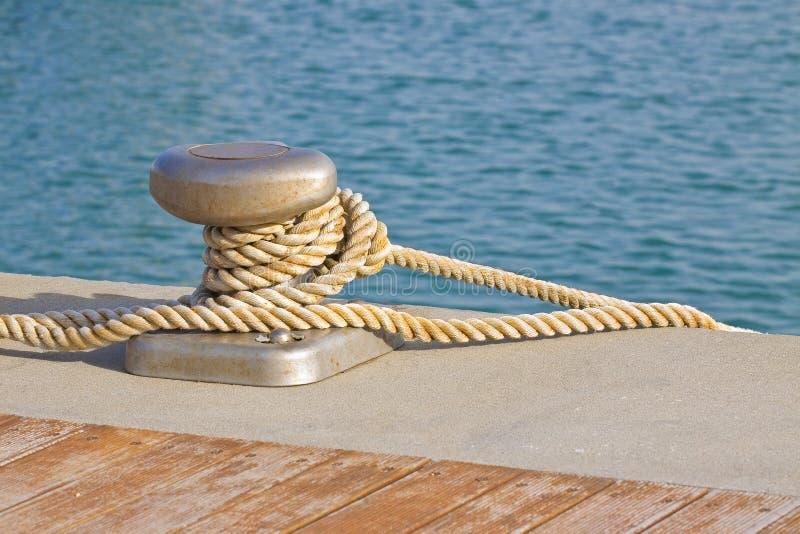 Cleat dla cumowniczych łodzi na drewnianej platformie przeciw wodnemu tłu obrazy stock