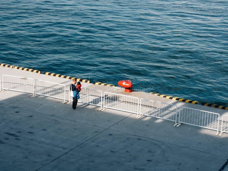 Cleat op de pijler in de haven Japan van Osaka Mens met een jong geitje op de pijler stock foto