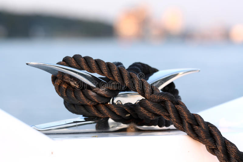 Cleat and rope, yacht detail. A black rope tied around a chrome cleat on a motor yacht royalty free stock photos