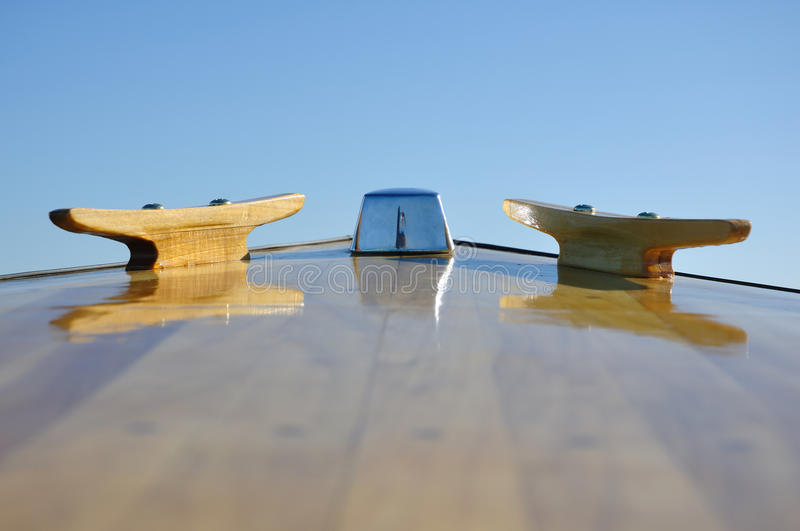Cleats on Bow Deck of a Wood Strip Boat. Against a Clear Blue Sky royalty free stock photography