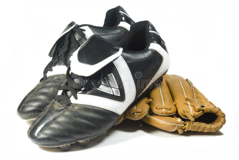 Cleats and glove. A pair of cleats and a baseball glove isolated on a white background stock photo