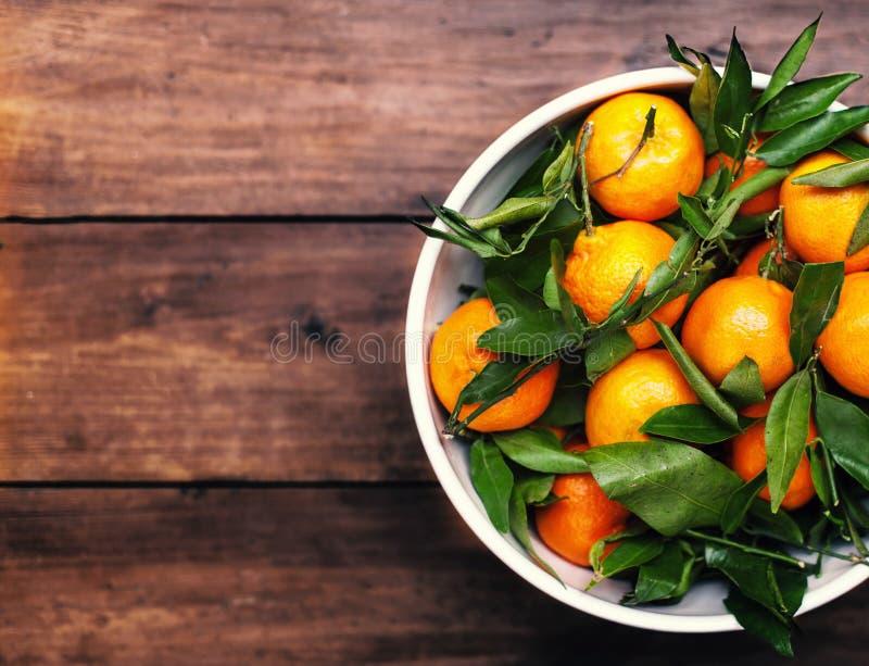 Clementina frescas da tangerina do mandarino na bacia branca sobre de madeira imagem de stock