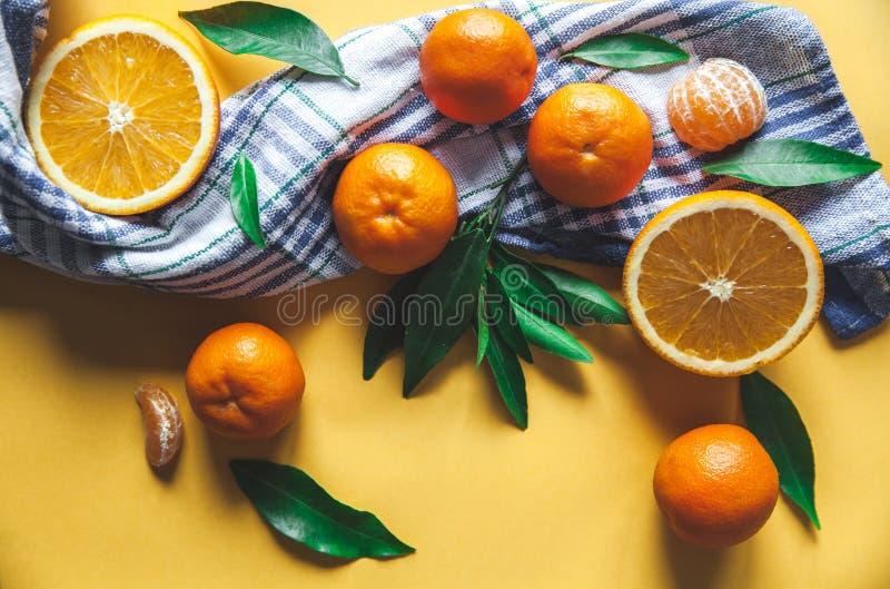 Clementine fresche, arance a bordo con le foglie verdi con un coltello Vista superiore su un fondo giallo fotografie stock libere da diritti