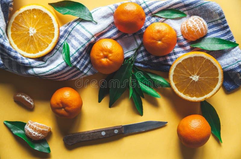 Clementine fresche, arance a bordo con le foglie verdi con un coltello Vista superiore su un fondo giallo fotografia stock libera da diritti