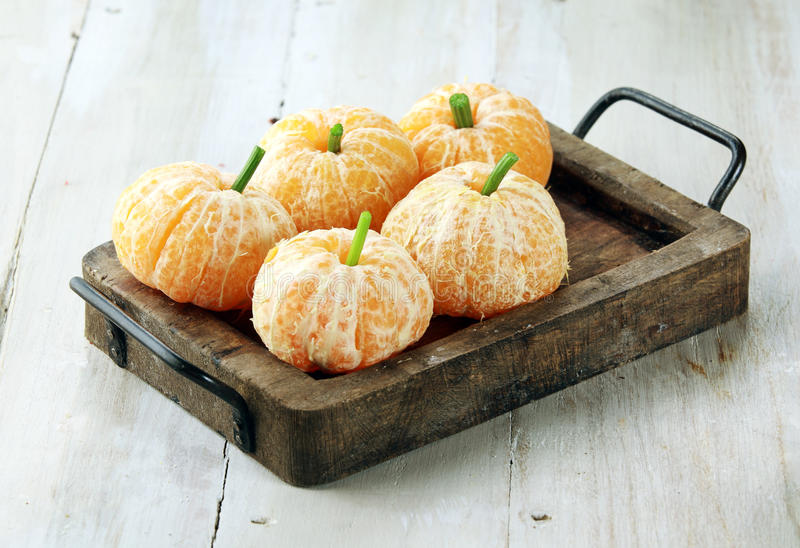 Clementine Oranges Decorated Like Pumpkins. On Rustic Wooden Tray royalty free stock images