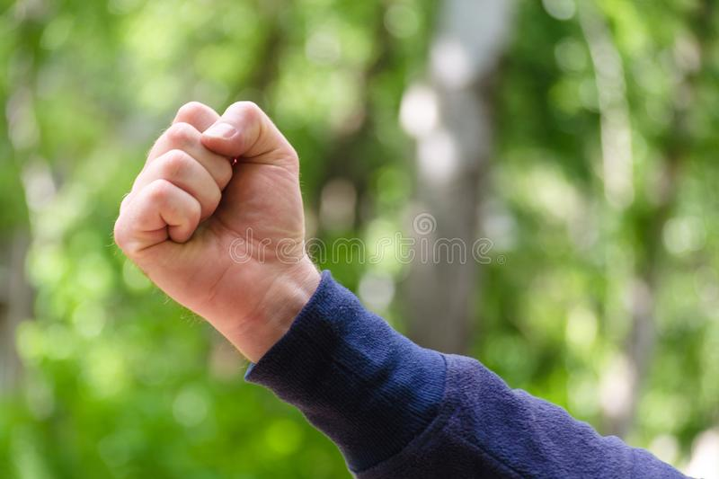 Clenched fist hand sign. Mens hand gesture of power and masculinity, success. Concept of brave, aggression, win. Close Up view on. Green nature background royalty free stock image