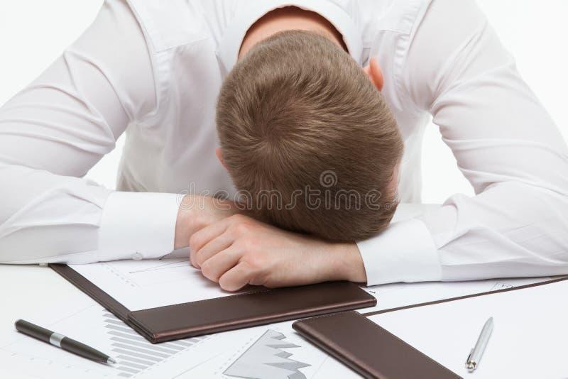 Clerck cansado que senta-se na tabela e que dobra sua cabeça, b branco fotografia de stock royalty free