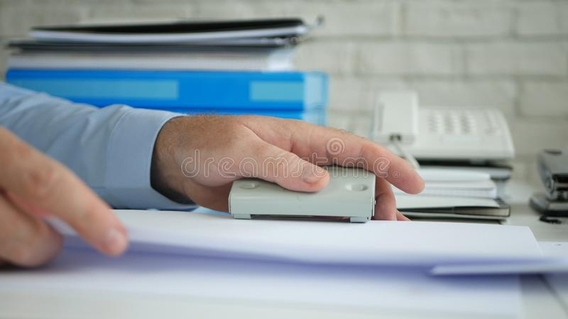 Clerk Workplace Activity Working in Archive Perforate Paper with a Hole Puncher stock photo
