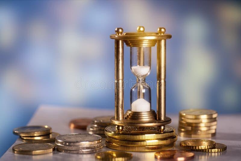 Clessidra con le monete fotografia stock libera da diritti