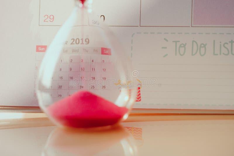 Clessidra a cristallo con la sabbia rossa sul concetto del calendario per tempo che si defila per la data importante di appuntame immagini stock