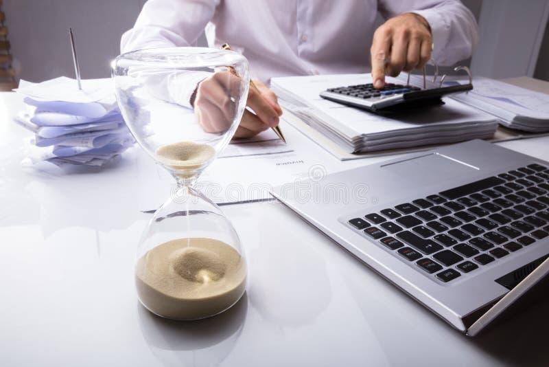 Clessidra di Calculating Invoice With dell'uomo d'affari immagini stock