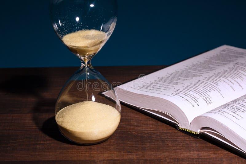 Clessidra e bibbia santa aperta fotografie stock