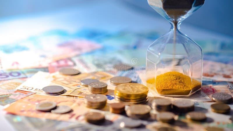 Clessidra e valuta sulla tavola, concetto di investimento di tempo fotografie stock libere da diritti