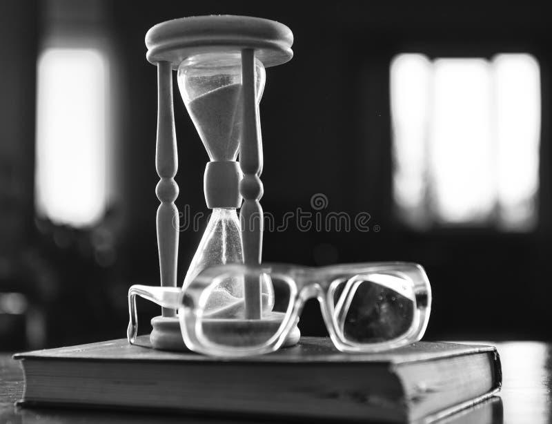 Clessidra, vecchio libro ed occhiali sulla tavola di legno, fondo scuro Concetto di flusso di tempo Clessidra di legno che conta  fotografie stock