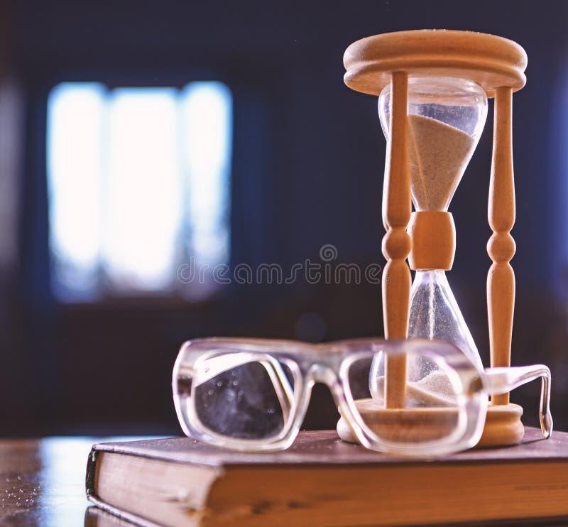 Clessidra, vecchio libro ed occhiali sulla tavola di legno, fondo scuro Sabbia che cade dentro della clessidra Flusso di tempo immagini stock libere da diritti