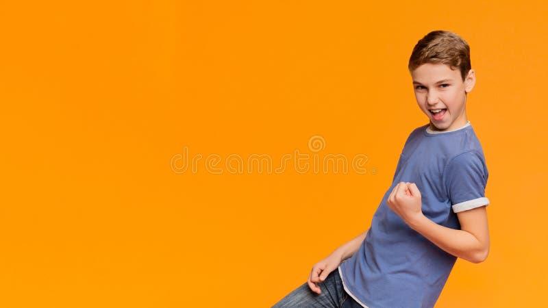 Cletching näve för upphetsad pojke som ja gör gest fotografering för bildbyråer