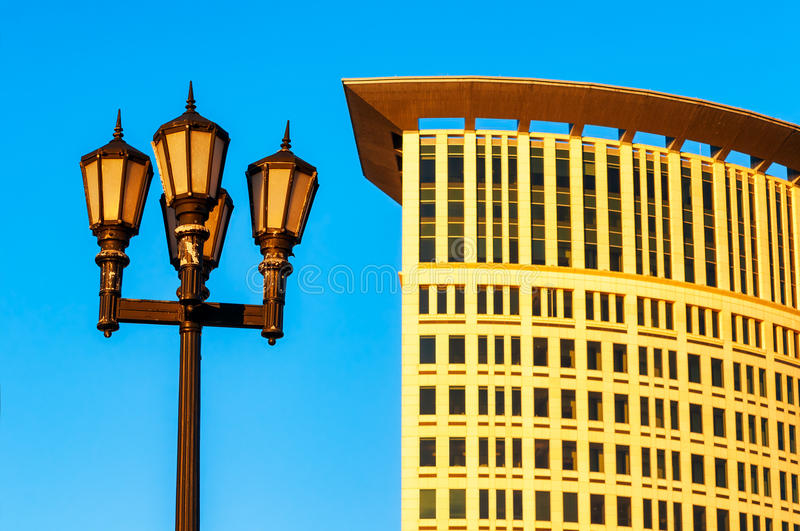 Cleveland contrast old and modern. CLEVELAND, OH - JUNE 17, 2016: An old-fashioned lamp post contrasts with the modern Justice Center early evening golden light royalty free stock photography