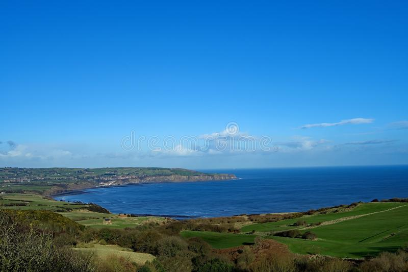 Cleveland Way view of Ravenscar golf course and Robin Hood`s Bay. This image captured on the Cleveland Way cliff top walk, shows a clear blue sky in February stock photos