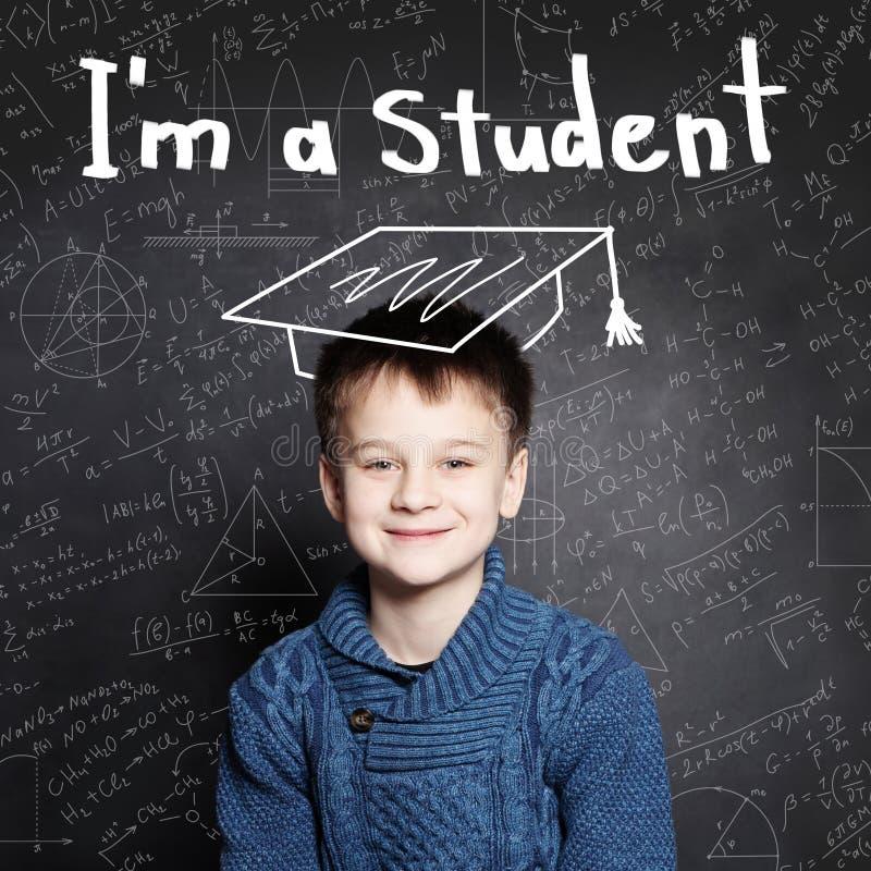 Clever boy pupil on blackboard background portrait. stock photos