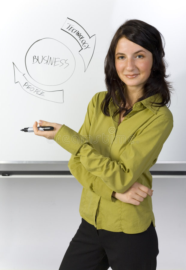 Clever businesswoman. Beauty businesswoman standing in front of blackboard. Smiling and holding marker. Looking at camera. Gray background stock photo