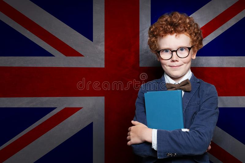 Clever child with book on the UK flag background royalty free stock photography