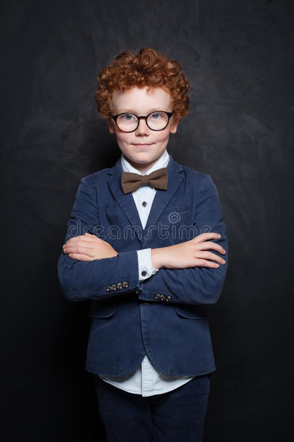 Clever child boy in glasses in classroom on chalkboard background. Smart student portrait royalty free stock image