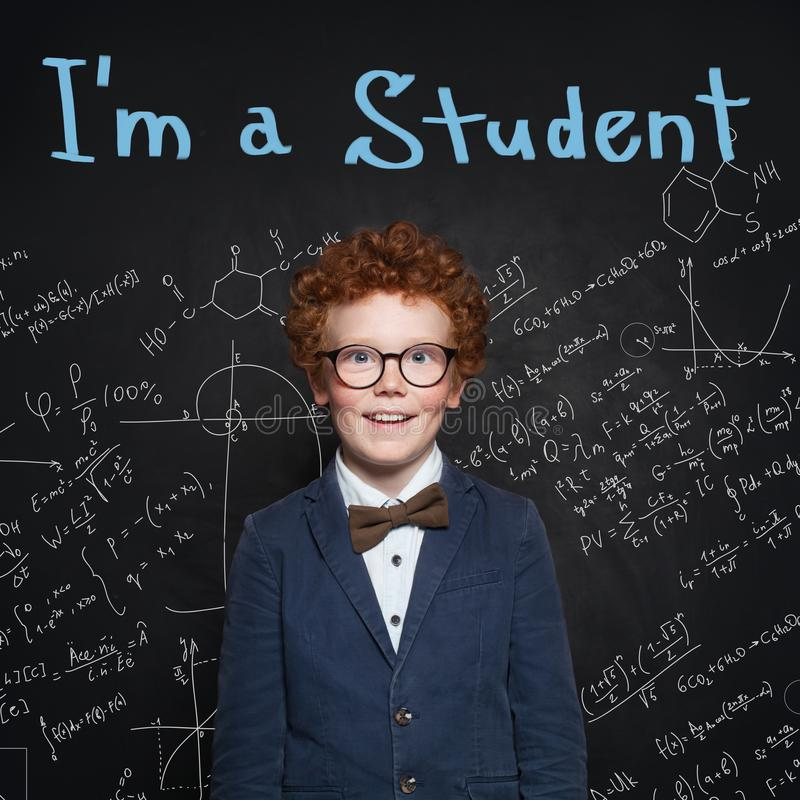 Clever child pupil on blackboard background portrait. Back to school stock images