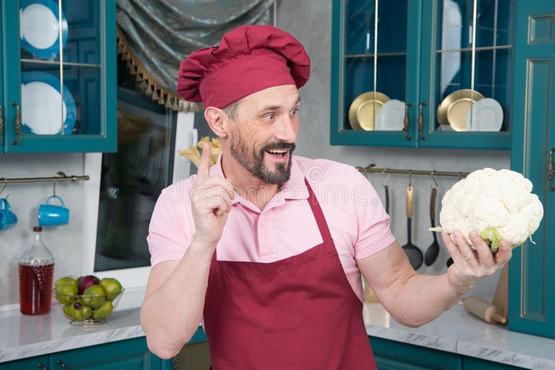 Clever funny chef with cauliflower. Man knows what to cook with vegetable. Cook pointing up by finger royalty free stock images