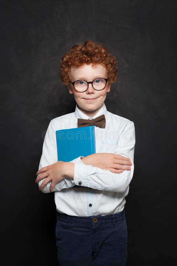 Clever kid with book on chalkboard background. Cute redhead child boy on blackboard portrait.  royalty free stock photo
