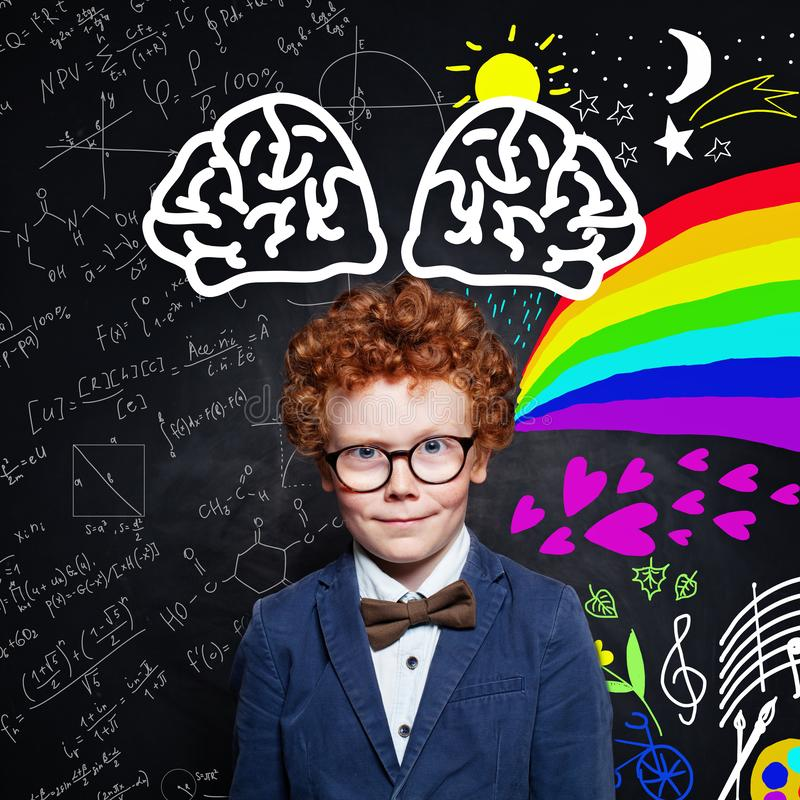 Clever little boy in glasses and student uniform on blackboard background portrait stock photo