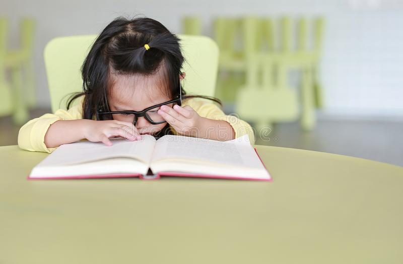 Clever little child girl wearing glasses intend reading a book in the kids room royalty free stock photos