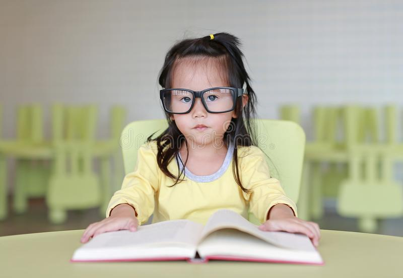 Clever little child girl wearing glasses reading a book in the kids room royalty free stock image