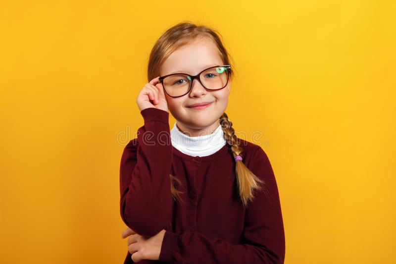 Clever little girl school girl corrects glasses. A child in a red sweater on a yellow background royalty free stock images
