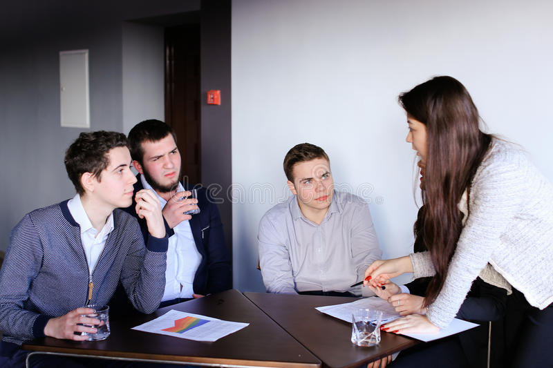 Clever men and young women quarrel and make up tasks for develop stock image