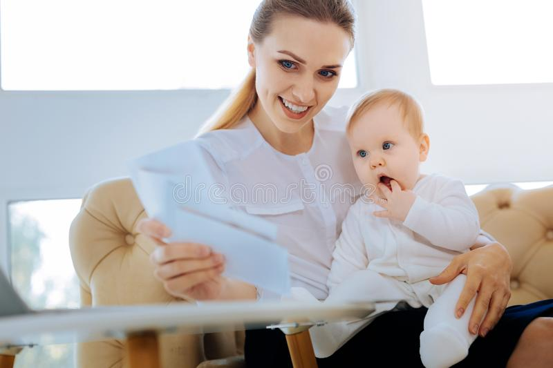Clever mother developing her child with special cards. Early development. Clever loving young mother working at the early development of her baby by showing him stock images