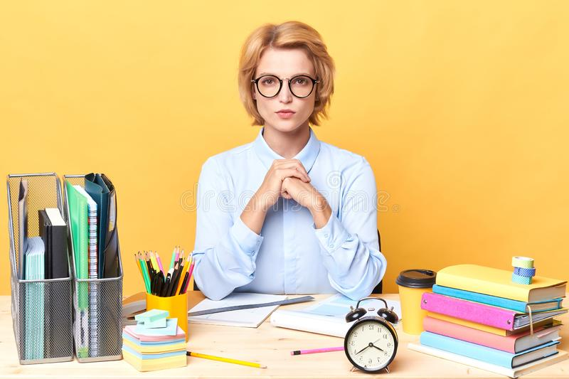 Clever pleasant woman in light blue shirt spending time in the office stock images