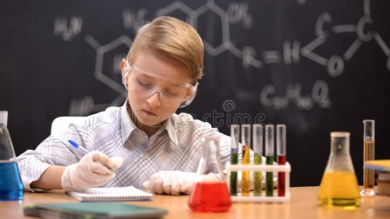Clever schoolboy conducting experiments and writing results at chemistry lesson royalty free stock images