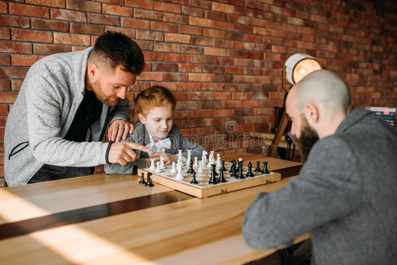 Clever schoolgirl playing chess with man stock images