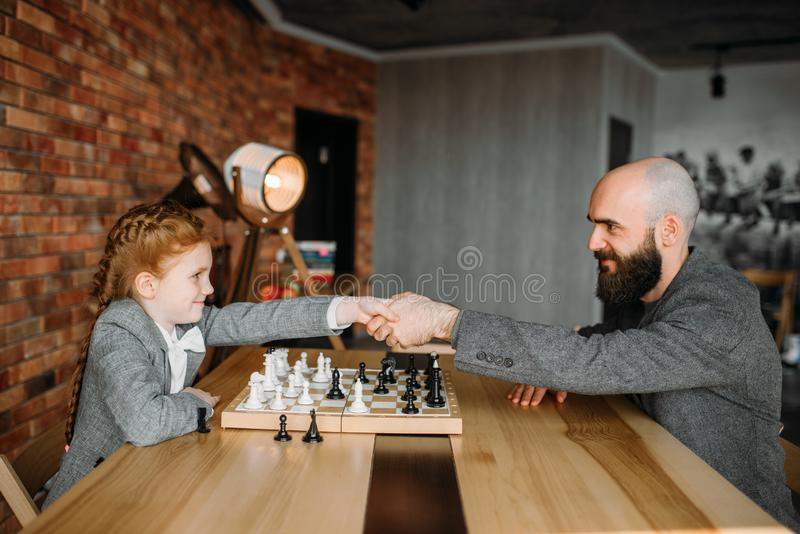 Clever schoolgirl wins the game of chess with man. Young girl at the chessboard, female kid plays logic game stock photos