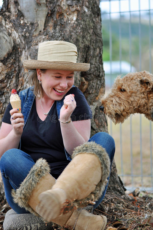 Clever sneaky pet dog sneaking up to pinch ice cream that pretty young girl eating. A lovely candid outdoors portrait of a cheeky , clever and very sneaky large stock photography