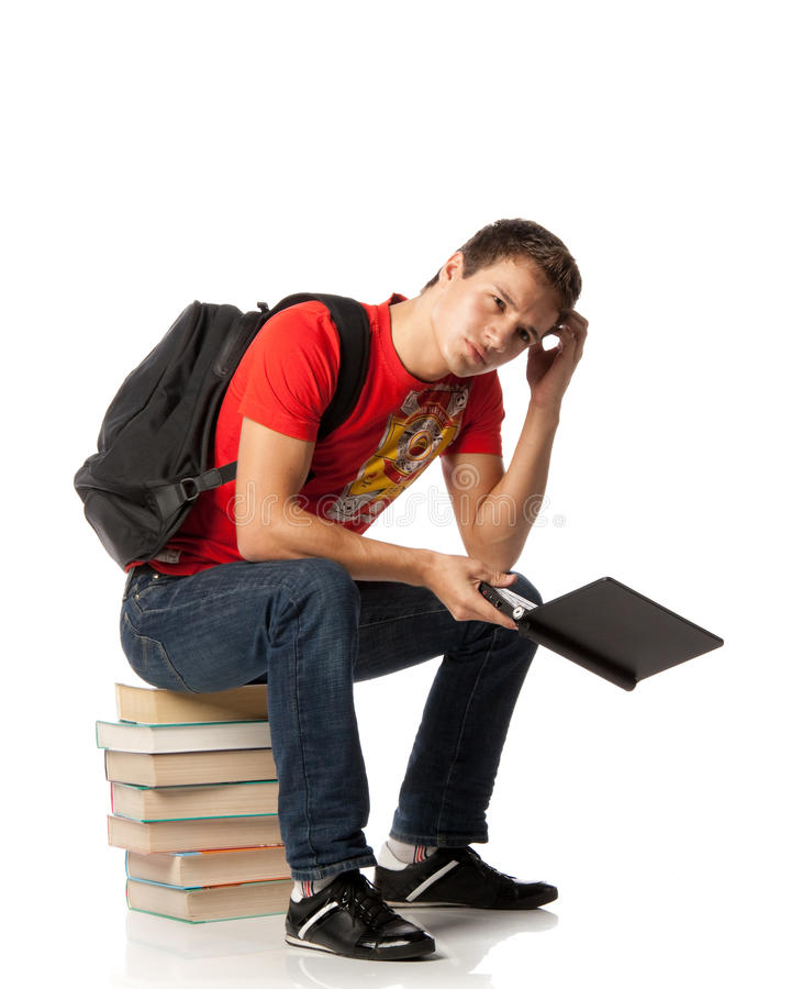 Clever student. The young man with the laptop sits on a pile of books on a white background royalty free stock photography