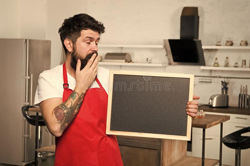 Clever ways to organize kitchen. Cook hold blank chalkboard copy space. Secret tips. Useful information. Man bearded. Hipster red apron stand in kitchen stock images