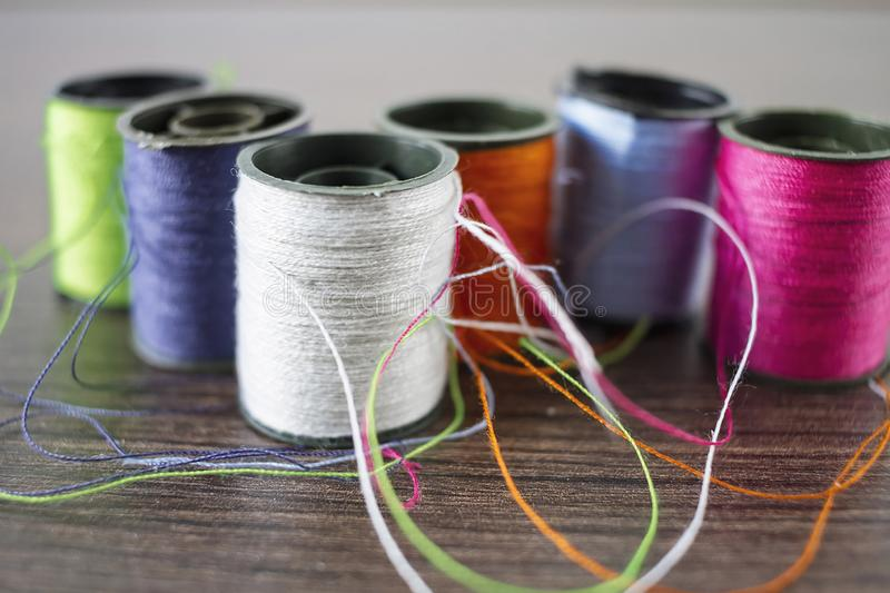 Clews of thread. Clews of colored thread over a wooden background stock images