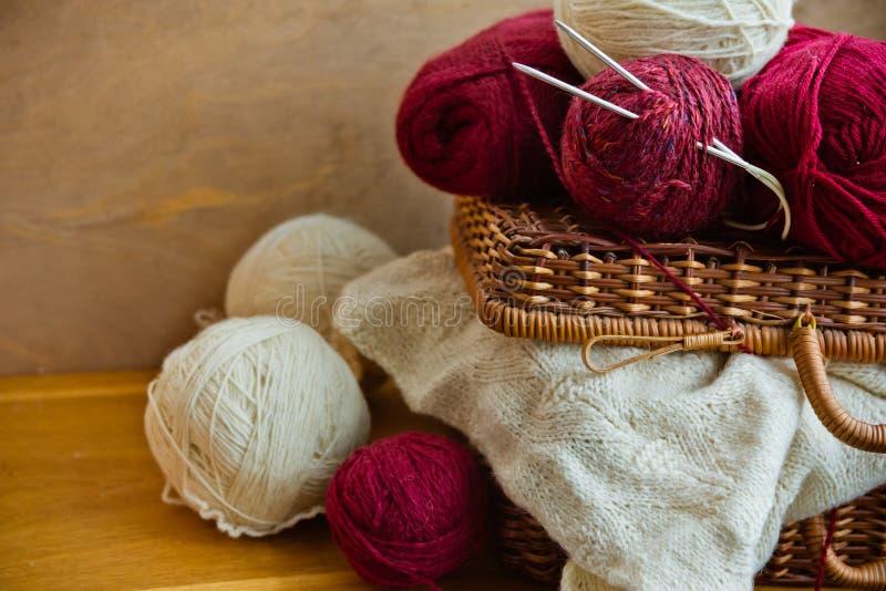 Clews das bolas da cesta de vime do vintage do fio de lãs branco vermelho, parte de bordado feito malha na tabela de madeira, faz foto de stock royalty free