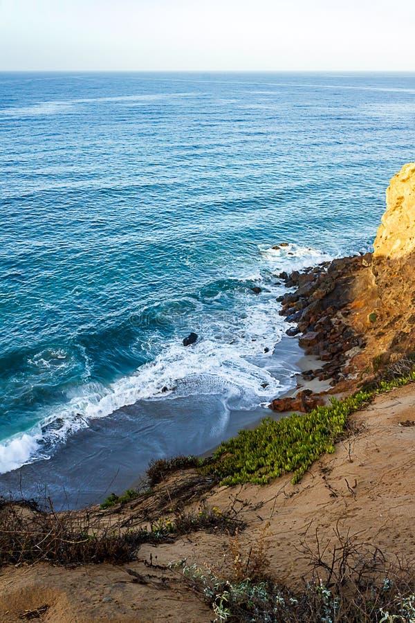 Clff zijaanzicht van vreedzame oceaan golvende kust en rotsen, van zandige iceplant gescherpte weg stock fotografie