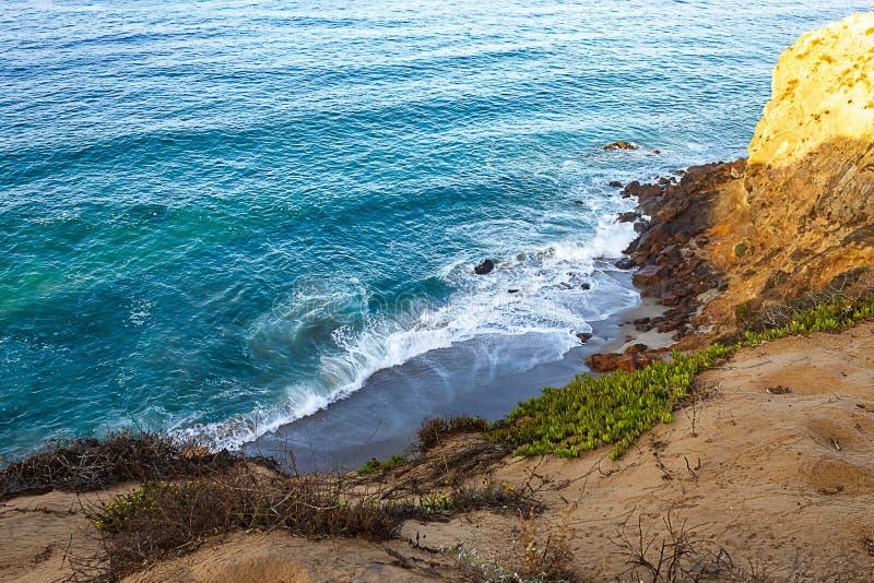 Clff zijaanzicht van vreedzame oceaan golvende kust en rotsen, van zandige iceplant gescherpte weg stock afbeeldingen