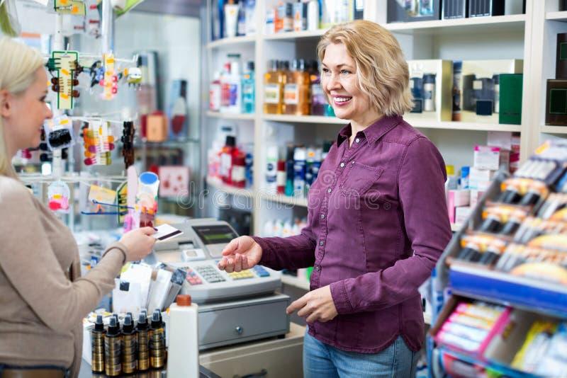 Cliënt die bij winkel bij kasregisterbureau betalen stock foto's